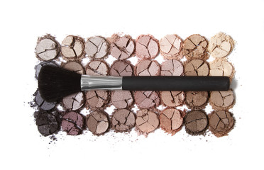 A broken eye shadow palette with large make up brush isolated on a white background