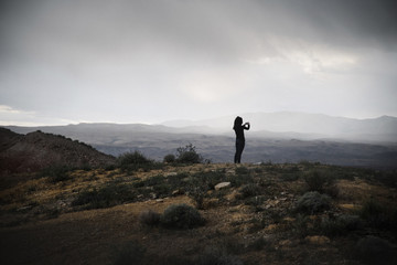 Woman standing in a prairie under a cloudy sky.