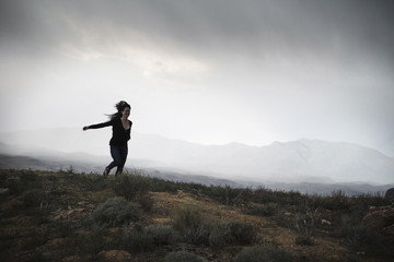 Woman running in a prairie under a cloudy sky.