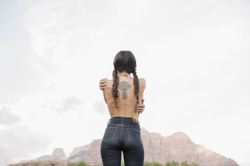 Rear view of a topless young woman with long brown hair in braids, wearing jeans, tattoo of a Celtic Cross on her back.