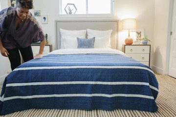 A woman smoothing a blue striped throw over a double bed in a bedroom.