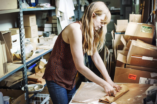 Woman with long blond hair standing in the store room of a shop, wrapping merchandise in brown paper.