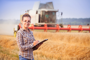 Pretty farmer girl in glasses with hair tied in a ponytail keeps a harvest accounting in the folder. Sunny day. Horizontal. Image released. Image released.