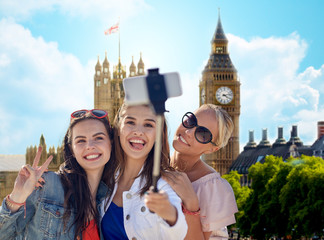 group of smiling women taking selfie in london