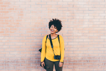 Knee figure of young handsome african curly black hair woman posing leaning against a wall, looking at camera laughing - serene, carefree, happiness concept