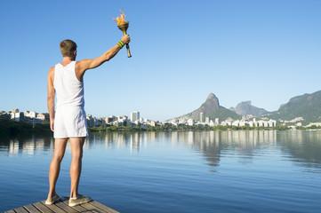 Torchbearer athlete standing with sport torch against the Rio de Janeiro, Brazil skyline at Lagoa Rodrigo de Freitas lagoon