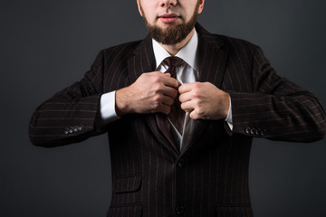 Attractive man in a suit lures, undresses and removes his tie