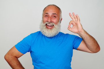 Aged man with white beard and broad smile showing OK gesture