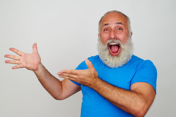 Senior white-bearded man delighted and pointing at something wit
