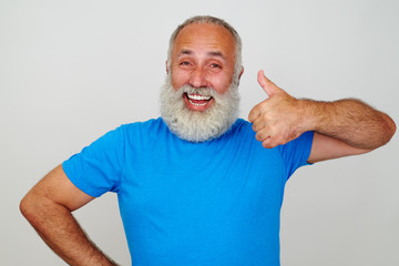 Smiling man with white beard showing thumbs up gesture against w