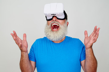 Smiling senior bearded male impressed while testing 3D technolog