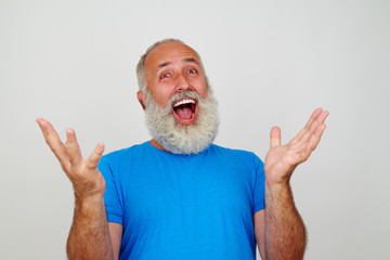 White-bearded senior male posing at the camera gesturing happine