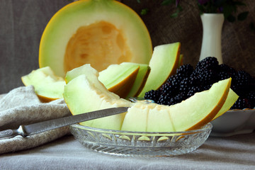 Ripe slices of melon and a plate with blackberries..