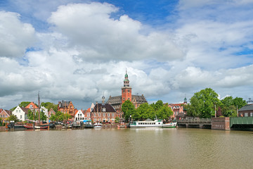 Leer, Germany. View from Leda river on City Hall in Dutch Renaissance style, Old Weigh House in Dutch classical Baroque style, Tourist Harbor with historical boats and Bridge of Erich vom Bruch.