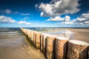 Wooden breakwaters on sandy Leba beach in late afternoon, Baltic