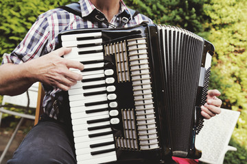homme senior jouant de l'accordéon dans nature