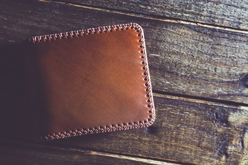 Men's leather wallet on wooden table