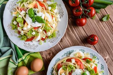 Spaghetti pasta salad with tomato, lettuce, egg, Feta cheese, green onion and sour cream