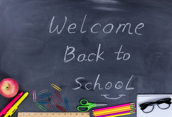 Back to school message with student supplies on chalkboard