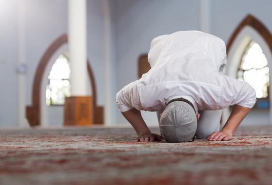 Religious muslim man praying inside the mosque