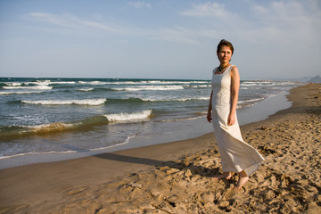 Beautiful short-haired woman in long white dress at the beach ne