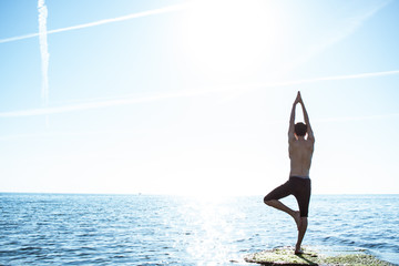 Male makes morning yoga exercise in sunlight