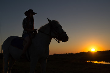 A cowgirl riding a horse on a ranch is silhouetted against the afternoon sun.