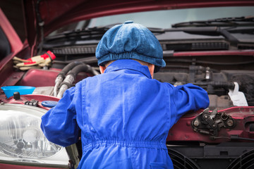 Little Mechanic / Little boy in blue workwear overall in front of open engine compartment doing some maintenance work at the car