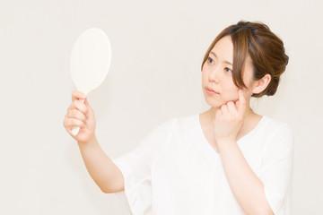 鏡を見る女性(美容イメージ)