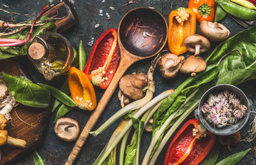 Various fresh vegetables with wooden cooking spoon for healthy  eating and nutrition on dark rustic...