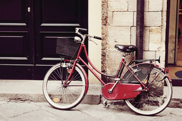 Red bicycle at the street of old town, Italy. Color toning applied.