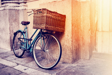 Retro bike with big basket on the old street of the city, Italy. Color filter applied.