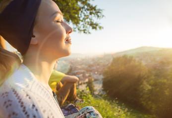 Carefree happy woman sitting on top of mountain edge cliff enjoy