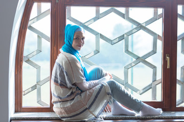 Beautiful woman with hijab sitting on the window in colorful outfit