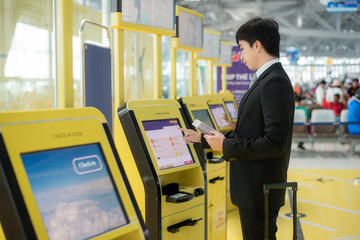 Business travel - Asian business man using self check-in kiosks