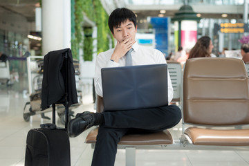 Asian business man using a laptop in airport.
