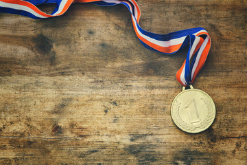 top view image of gold medal over wooden table