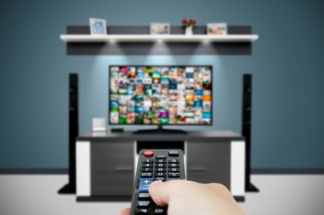 Watching television in modern TV room. Hand holding remote