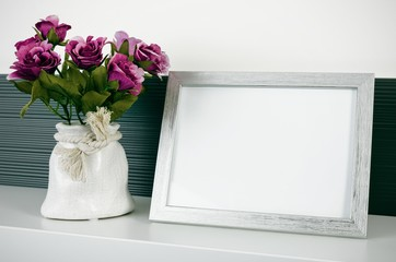 Photo frame stands on a shelf next to the flowers