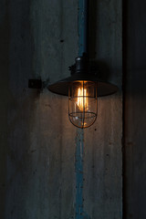 A classic Edison light bulb on old wall background switched on.
