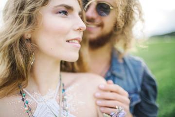 Young beautiful hippie couple walking in green summer field