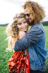 Young beautiful hippie couple walking in green summer field