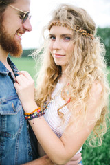 Young hippie male with beard hugging curly female outdoors