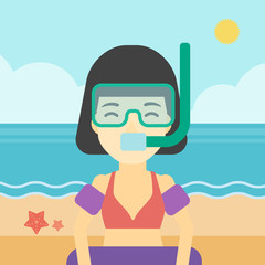 Woman with snorkeling equipment on the beach.