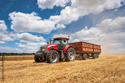 Wall mural Modern red tractor on the agricultural field on sunny summer day