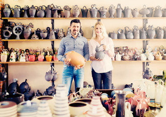 portrait of man and woman shopping ceramic utensil in boutique