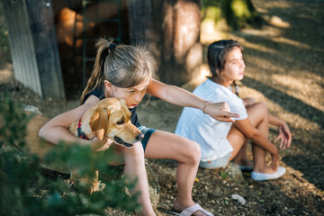 Girl pointing and hugging her dog on a playground