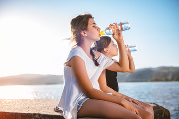 Two girls drinking water and sitting on dock