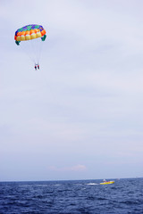 parasailing in summer beach by speed boat, vertical composition