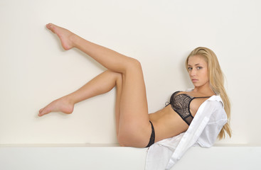 Stunning young blonde woman wearing black lingerie and white men's shirt poses on small ledge